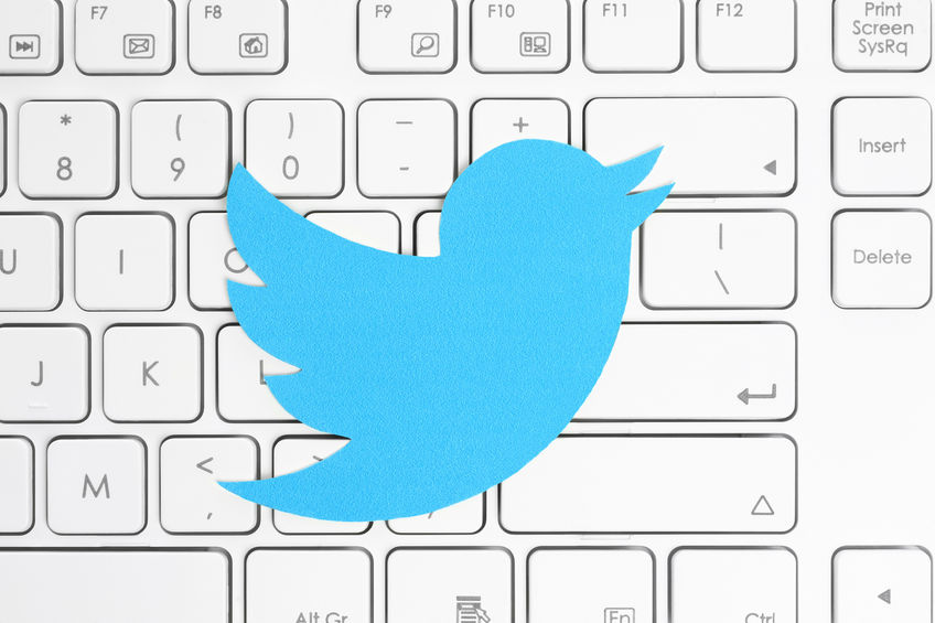 39070379 - kiev, ukraine - april 15, 2015: twitter logotype printed on paper and placed on white keyboard. twitter is an online social networking service that enables users to send and read short messages.